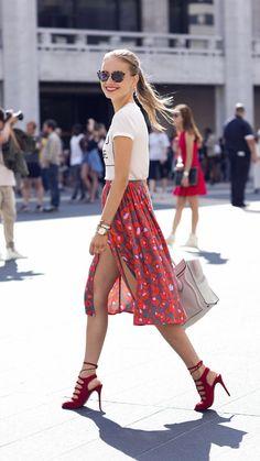 Comprar ropa de este look:  https://lookastic.es/moda-mujer/looks/camiseta-con-cuello-barco-falda-a-media-pierna-sandalias-de-tacon-bolsa-tote-gafas-de-sol-pulsera-reloj/8279  — Gafas de Sol Azul Marino  — Camiseta con Cuello Barco Estampada Blanca y Negra  — Pulsera Dorada  — Reloj Dorado  — Falda a Media Pierna Estampada Roja  — Bolsa Tote de Cuero Blanca  — Sandalias de Tacón de Ante Rojas