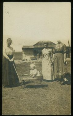 Farm women taking baby for a wagon ride...love it! Note there isn't a tree in sight.