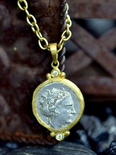 "Greece 3rd century BC15mm silver coin is set in 22k yellow gold with two white diamonds 0.04cts..  It hangs from a handmade 18"" chain also made of 22k yellow gold.This small silver coin depicts an ancient nymph caregiver who protected and cared for Hera, goddess of love and marriage, when she was a baby."