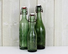 This is a beautiful set of 3 antique French tall glass bottle manufactured in France. It date from the 1950s and used in French cafes and breweries for serving the lemonades and beers.  Stopper are in genuine porcelain. LIMONADE EA CHAMBERY ( Savoie ) BRASSERIE VIDAL BEDARIEUX FABRIQUE de BOISSONS GAZEIFIEES - BEZIERS -ALVERNHE & Cie  The metal parts have a beautiful patina. Bottles are leaking but the porcelain cap closes very easily.  Bottles are in dark green blown glass