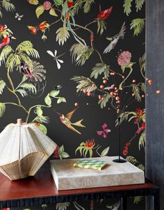 What better way to create contrast than a black wallpaper with vibrant bird and flower motifs on it.