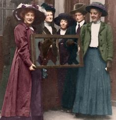"""Militant British suffragettes smile at a window broken during their 1912 window-smashing spree in which disgruntled suffragettes demanded that shop-keepers in London's best neighborhoods actively support votes-for-women. Hundreds of women ended up in prison! Find out what happened next in """"Two Presidential Mistresses and the Battle for Votes-for-Women"""" by VA Harrington Hutton. Photo COLORIZED by CoffeebreakReaders. Buy the book!"""