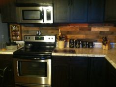 Pallet backsplash in our old farm house kitchen highlighted by white and black countertops and lighting under the cabinets
