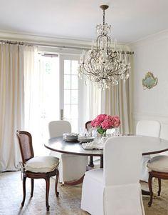 """Understated Dining Room    Hot pink hydrangeas bring the dining room alive, and the mix of cane-back and slipcovered chairs keeps it interesting. The walls above the wainscoting are stenciled with a clear glaze in a historical pattern, Troupe Square, from Whitewall & Co. An antique beaded-crystal chandelier """"has an ethereal quality that doesn't overpower this small room,"""" Schnell says."""