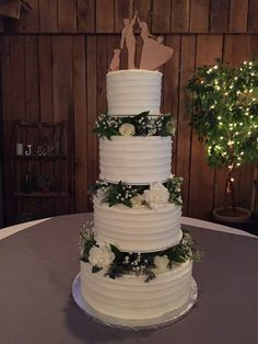 Four tier textured buttercream wedding cake with separations filled with fresh flowers.