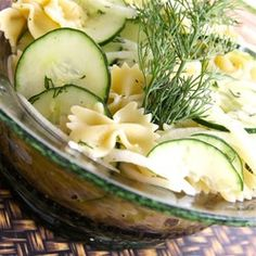 A simple vinegar dressing coats cucumber and onion slices and bow tie pasta for a cool cucumber salad.