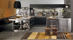 Who says stainless steel has to be cold? Here, an Arclinea kitchen in stainless steel is warmed up with wood cabinetry and accessories, plus warm decorative elements. A variety of design elements make this kitchen timeless and welcoming. #ArclineaNY