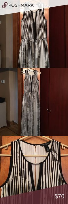 White House Black Market maxi dress NWOT! Gorgeous white with black vertical stripes. V neck with silver accent. Long key hole on the back. Has elastic waist for some give. Has a half slip for non see thru. Also has two slits on each side for easy walking. Chest side to side is almost 17 in. 58 in length. So classy for any event. Price is firm White House Black Market Dresses Maxi