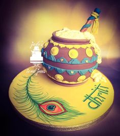 This cake is a pot full of butter with a flute and peacock feather which all symbolises Krishna.