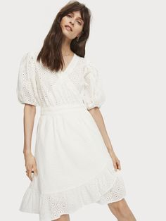 Scotch & Soda Cut in a feminine silhouette, this romantic wrap dress is adorned with a delicate broderie anglaise pattern. It's designed with a ruffled hem, and puff sleeves with elasticated cuffs. The v-neck is secured in place with a hook and eye fastening.