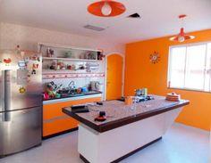 Ao mudar para uma casa, Carminha de Queiroz, que sempre viveu em apartamento, fez questão de uma cozinha ampla, com uma ilha no meio do ambiente para o cooktop. O ambiente, de 16 m², traz cores fortes nas paredes e nos armários.