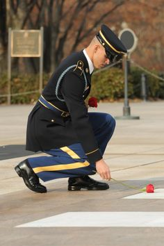 3d U.S. Infantry Regiment (The Old Guard) Sgt. Shane Vincent, Tomb Sentinel, Tomb of the Unknown Soldier, 3d U.S. Infantry Regiment (The Old Guard), places a rose at one of the four crypts of the Unknowns during his last walk ceremony, Nov. 30, in Arlington National Cemetery, Va. Placing a rose at the foot of each crypt signifies a Sentinels' last and final honor before they leave the Tomb. Vincent served at the Tomb for 54 months. (U.S. Army photo by Sgt. Luisito Brooks)