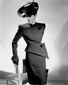 black dress with black hat and feathers with buttons at one side, geometric cut to one side, and short skirt