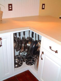 Use screw-hooks in the top of an awkward corner cabinet to turn it into a pot rack. | 31 Insanely Clever Ways To Organize Your Tiny Kitchen