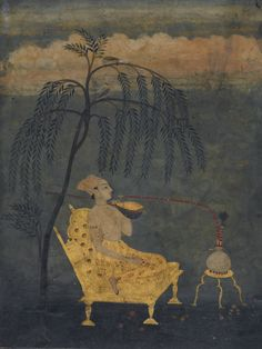 An elegant youth seated on a day-bed holding a sitar and smoking a from a huqqa, Rajasthan, Bikaner, India. he. 18th C.