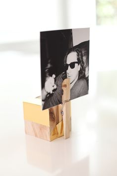 DIY place card holder made from a block of wood, a clothespin and gold metallic contact paper.