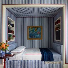 A built-in bed with shelving and striped wallpaper makes a great guest bedroom @katieridderinc.