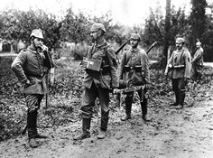 A German soldier holds the handset of a field telephone to his head, as two others hold a spool of wire, presumably unspooling it as they head into the field.
