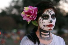 Cynthia Ramirez (center) stands with her face painted for All Souls Day as she listens to a mass given by Archbishop Gustavo Garcia-Siller at San Fernando Cemetery No. 2 on Wednesday, Nov. 2, 2011. Ramirez said the face painting was a Mexican tradition and she did it to pay respect to her grandparents who were laid to rest at the cemetery. Ramirez was joined by hundreds of other families who went and paid homage to their loved ones. Photo: Kin Man Hui, KIN MAN HUI/SAN ANTONIO EXPRESS-NEWS…