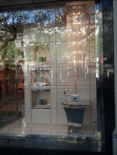 JIMMY CHOO; en Paseo de Gracia nº97, Barcelona; Presenta un escaparate acorde con la filosofía de la marca: elegancia y feminidad (transmitido mediante el color perla beige y los brillantes de los artículos y de la lámpara de techo que se deja caer como una lluvia de glamour); Composición dividida en 2: en la parte derecha está el producto exclusivo ya que se ubica encima de una mesita y debajo de la lámpara, y como secundario, la parte izquierda cuyos artículos se encuentran más hacia…