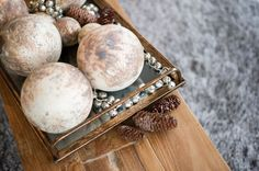 Style your interior with elements from the outdoors for a rustic twist on holiday decor. Use a tray to display things like pinecones, ornaments and bells. Find this and more decor inspo at CF Interiors.