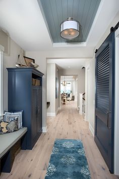 This beach house features fine finishes and rich trim details including wainscot and various painted ceilings. Navy cabinets are Benjamin Moore Deep Royal 2061-10. The wall is Benjamin Moore Revere Pewter and ceiling is Benjamin Moore White Dove. The inset is Benjamin Moore Kentucky Haze.