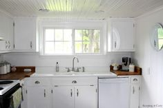 Country Kitchen With DIY Reclaimed Wood Countertop look at the cabinets- classy slab front.