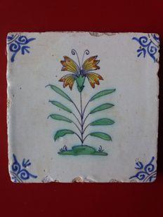 Antieke polychrome tegel - bloem op grondje