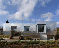The UK's Paul Archer Design is the firm behind Green Orchard - a sleek, eco sustainable home, starting with the views. This 2,150-sq.-ft. house sits  on over 28,000 sq. ft. of landscaped gardens in South Gloucestershire overlooking the Severn Estuary. Zero carbon house features passive systems that let it operate efficiently and eco-consciously. It's all wrapped in mirrored panels reflecting  the surroundings and render it virtually invisible. Minimalist interiors reflect the home's eco…