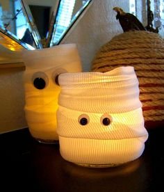 Cute, cheap Halloween decorations: These mummy candle holders are made with Mason jars, dollar store gauze, and googly eyes.