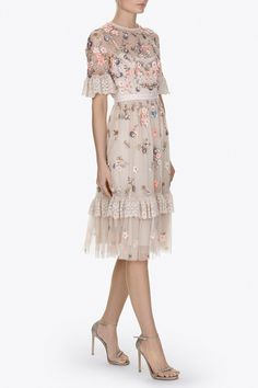 The Ditsy Scatter Dress has a flattering, fitted bodice with a fuller tulle skirt. The bodice fabrication is semi sheer tulle with an integrated camisole slip lining, finishing with our signature grosgrain trim at the waistband. Prairie inspired ruffle trims are featured on the sleeve and lower skirt in delicately embroidered tulle with lace inspired motifs. The Ditsy Scatter artwork is inspired by vintage ditsy fabric prints with pretty bunches of flowers. These are depicted in soft…