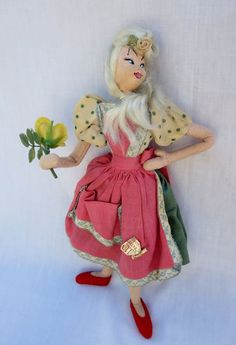 """Vintage felt Klumpe doll, 10"""" made in Spain, has the paper Klumpe tag on the back of her skirt and part of the (torn) foil tag on the front. She is holding a plastic flower and has a silk rosette in her hair."""