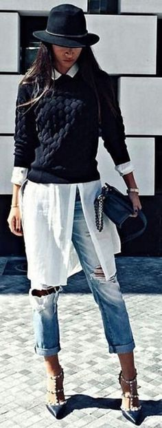 Black sweater over white tunic and light blue jeans.