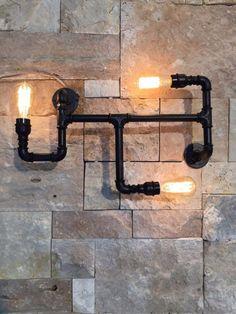 Aplique de pared fabricado con cañería de acero reciclado de obras antiguas