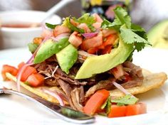 Cola Pork Tostadas, with avocado, cilantro, red onions and tomatoes over crispy tortillas, yumm!- Que Rica Vida