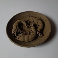 Prawn sculpture on a plate done with natural clay and then dried for terracotta firing.