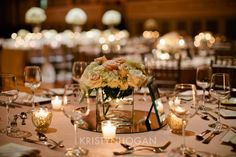 white and blush centerpiece on a mirror with candles