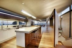Kitchen: window + cupboards above.  Island bench: no sink, timber veneer facade underneath.