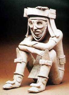 His costume is unlike that seen in any other Mesoamerican portrayals and his expression, even though partially obscured by the eye rings that some scholars connect with the Aztec Rain God Tlaloc, radiates a sense of quiet, internalized contemplation. Is he human, perhaps a young lord, or is he a god? (Height: 47 cm.) Photograph by Antonio Vizcaíno, published in Museo de Antropología de Xalapa, Xalapa, Veracruz, México, 1988.   Seated male sculpture