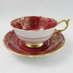 Beautiful tea cup and saucer by Paragon. Extensively and intricately decorated with gold. In the centre of the tea cup is a large gold medallion. Both cup and saucer are a deep red color. Gold trimming on cup and saucer edges. Set is in excellent condition (see photos). Markings read: