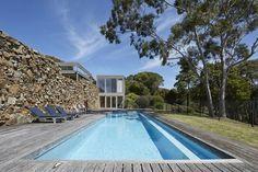 Casa de vidro e pedra com piscina azul na austrália