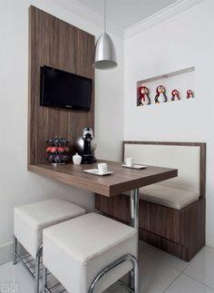 """""""Optamos por uma área de refeições compacta, mas gostosa de ficar"""", diz Bruna Mello. O sofá (1 x 0,47 x 1 m), com inspiração nas lanchonetes americanas, reúne acolchoado de courino e base de MDF no padrão Gris Montano (Duratex) – o mesmo material compõe a mesa (1 x 0,70 x 0,75 m), o painel (0,70 x 1,35 m) e as jardineiras de temperos (40 x 16 x 20 cm). Um nicho no drywall expõe a fofa coleção de pinguins…"""