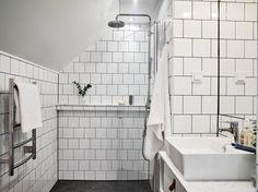 Det helkaklade badrummet som med sina naturliga färgval blir tidlöst. Små detaljer som att sätta de enkla (och billiga) 10×10 kakelplattorna i tegelförbandoch den lilla hyllan med Carraramarmor gör underverk för intrycket.