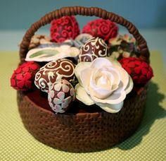 cesta de bolo de chocolate com ovos de chocolate e flores em açucar