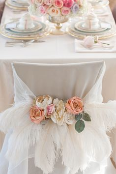 Beautiful Wedding chair decor in Peach + Cream with feathers.  Photography: Krista Fox - www.kristafox.com