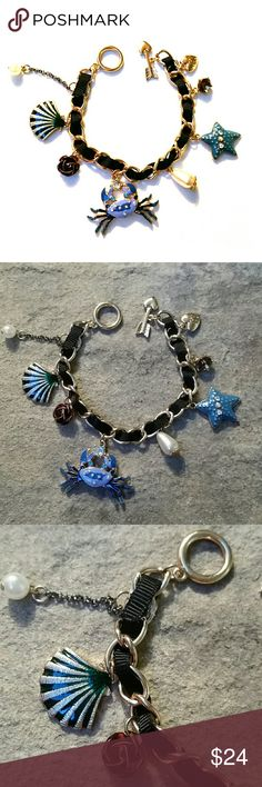 """Betsey Johnson Blue Charm Bracelet Crab & Shell NWOT Betsey Johnson blue ocean life charm bracelet featuring a crab, starfish, sea shell, flower, pearls,  crystals, and of course the BJ heart ?.The metal is a shiny gold with a black ribbon woven through, toggle arrow closure. The photos really don't do it justice! Measures 7"""" without closure hardware.  Thank you for checking out my closet, and happy poshing!! :)   SORRY, NO TRADES AT THIS TIME. Betsey Johnson Jewelry Bracelets"""