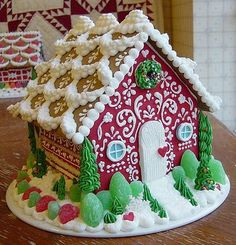 I love the thick royal icing snow drifts/shingles on the roof.  The icing evergreen trees on the corners are a nice touch, too.