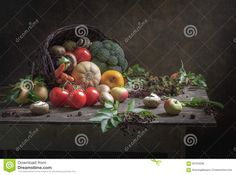 Still Life Gifts of autumn, cornucopia, healthy food, with a large wicker basket, from which poured vegetables, fruits and mushrooms mushrooms, pumpkins, tomatoes, carrots, eggplant, apples, twigs blackberry and elderberry with berries on a dark plank table on a dark background