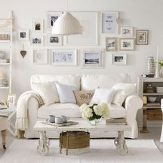 salon blanc aménagé avec des meubles shabby chic blancs et décoré d'images en cadres blancs