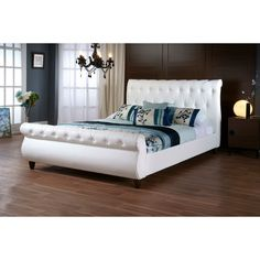 The queen-sized Ashenhurst Designer Bed is constructed with an engineered wood frame, foam cushioning, and soft matte White faux leather upholstery.